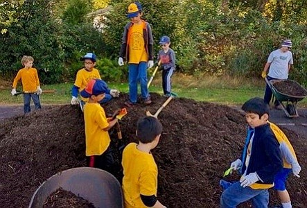 Clockwise from right: Pack 665 members Christian Cunningham, Amrit Singh, Robert West, Justin Grant, parent Van Avondolio, Magnus Avondolio, Carlos Janada, Max Avondolio and Tyler West, help shovel some mulch into wheelbarrows for use in the beds near the butterfly garden.