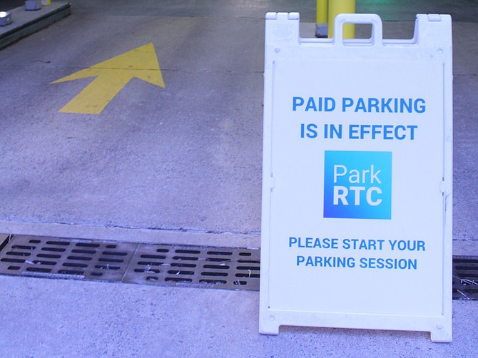 Signs stand outside the entrances of the shopping center's parking garages to remind people that paid parking is in effect. An employee was also standing near the first-level pay station to help people navigate the machines.