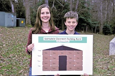 Laura Whittle and her son Sebastian Whittle, a 4th grader at Dominion Christian School, holding a poster indicating funds raised for the Uzimatele Educational Centre mission project in Nairobi. 