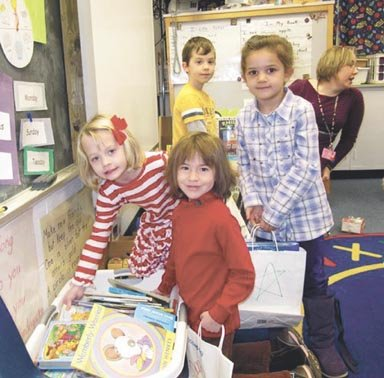 Churchill Road kindergarteners Arden Williamson, Tenley Overdeck, Jwana Al-Shihabi, and Evan Poulos fill gift bags with school supplies, while their teacher, Erin Thurston, looks on.