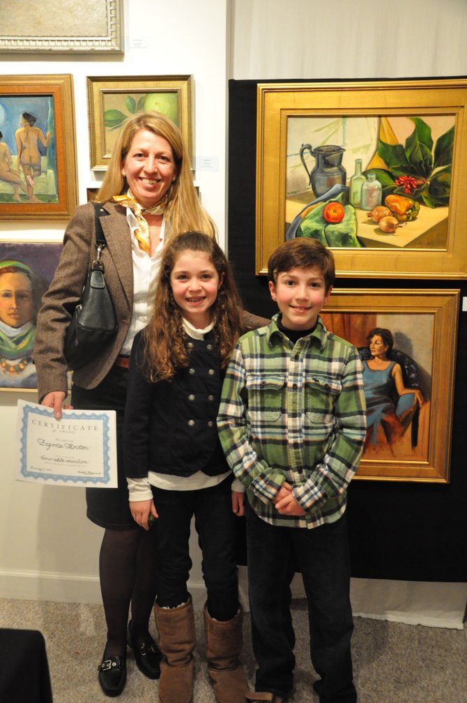 "Artist Begoña Morton and her children Miriam, 8 and Thomas, 11, in front of her paintings ""Message Bottles"" (top) and ""Portrait of Livia"" at the Great Falls School of Art. Morton won an honorable mention for both paintings and second place in the adult category for her painting ""Nautilus"" Saturday, Jan. 7 at the school's second annual show."