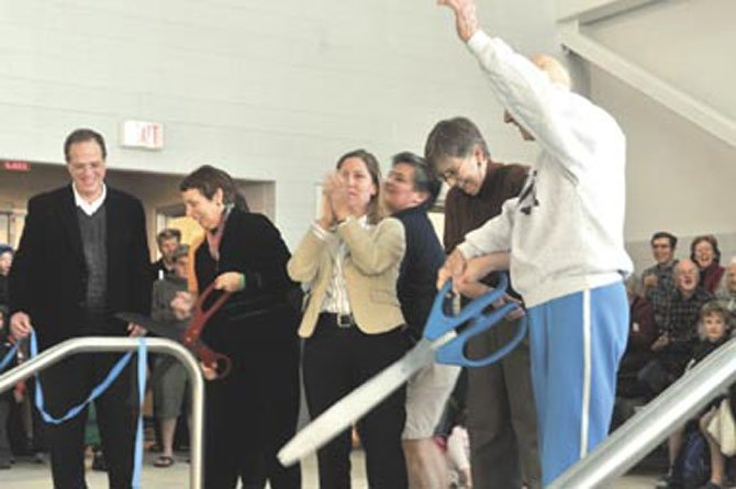 From right, George Strollo, Arlington County Board Chair Mary Hughes Hynes, School Board members Abby Raphael, Libby Garvey and School Superintendent join with others to cut the ribbons to the newly opened center.
