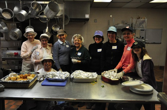 Volunteers from Thomas a Beckett Catholic Church prepare dinner at St. John Neumann Catholic Church for the homeless people staying the night as part of the FACETS Hypothermia Prevention Program.