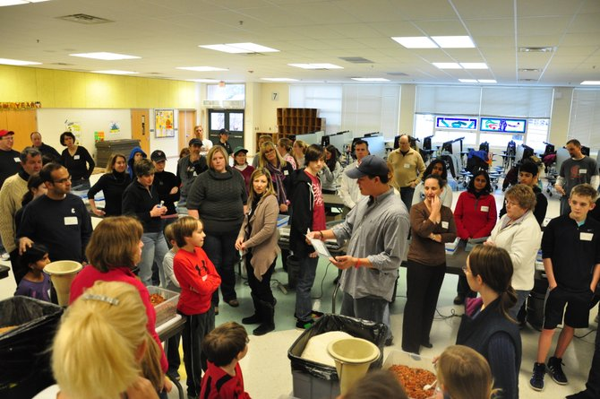 Dominic Alexander of Stop Hunger Now shows hundreds of volunteers how to package nonperishable meals to be send to starving people around the world at Colvin Run Elementary School Sunday, Jan. 22. The volunteers packaged more than 25,000 meals during the event.