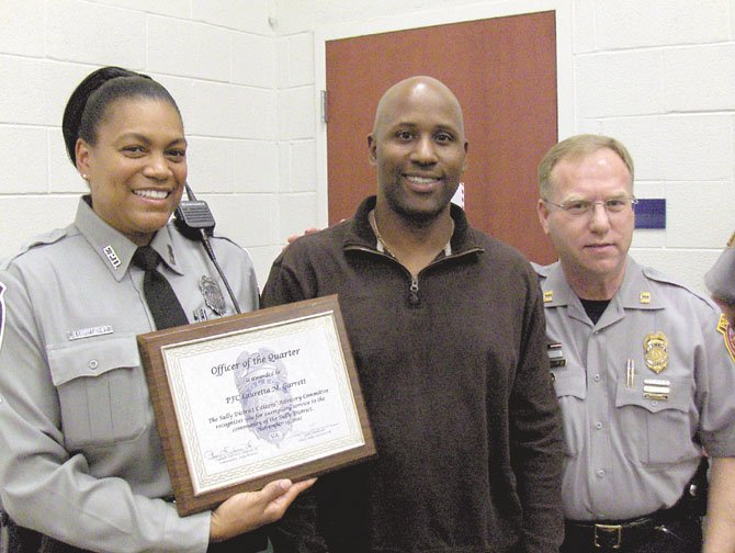 From left are Pfc. Lauretta Garrett; her husband William, a battalion chief with the Fairfax County Fire Department, and police Capt. Purvis Dawson, commander of the Sully District Station.