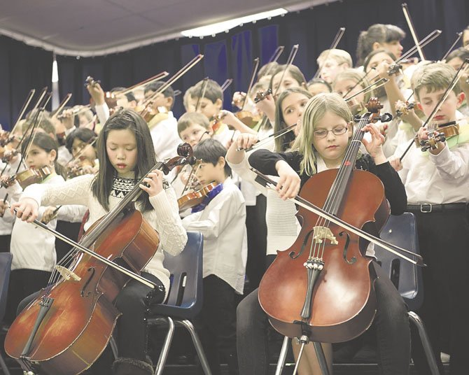 Adaline L. and Isobel Cobb, with 86 of their classmates, warm up on their cellos. The 88 beginners, in addition to their 54 colleagues in the Advanced Orchestra, delighted the audience of parents, family and staff with 10 tunes.