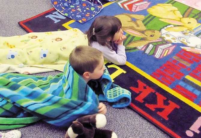 Alex Jones, 3, and friend Sarah Mace, 4, of Springfield, snuggle in their blankets to listen to librarian Twyla Turner read winter-themed books during Twilight Tales at Kings Park Library in Burke Tuesday, Jan. 24.