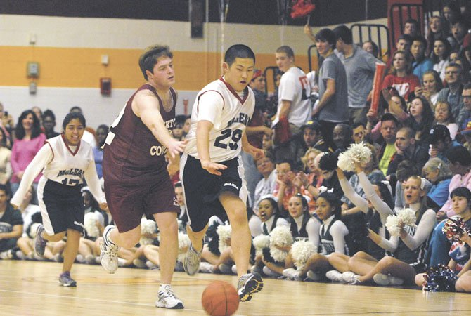 McLean's Dylan Kim drives down the court while being pressured by Oakton's Matt Nelson during Fanquest 2012, which featured a game between McLean and Oakton High School Special Olympics Athletes.