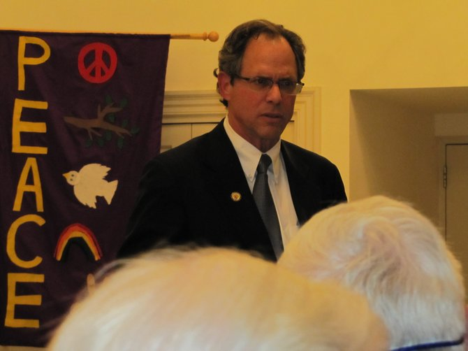 County Council President Roger Berliner faced an angry crowd in Potomac last week, in contrast to the banners behind him.