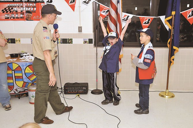 Cubmaster and Pinewood Derby emcee Andrew Gallotta awards Best Design medals to Bear Scouts Aidan DeVore, with arms raised in celebration, and Jackson Tomasco at Pack 1965's Pinewood Derby.