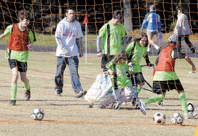 Alexis Kende and Mary Cassell, in the middle, participate in a soccer game with other athletes of the TOPSoccer program in November at Wootton High School. Youth with all disabilities, including those in walkers, participate in the program, despite the difficulty getting around grassy and often muddy fields in their walkers. TOPSoccer is exploring the possibility of using the old inline skating rink (main photo) at the Potomac Community Center for its programs, which would allow all of the athletes to compete without difficulty do to their equipment.