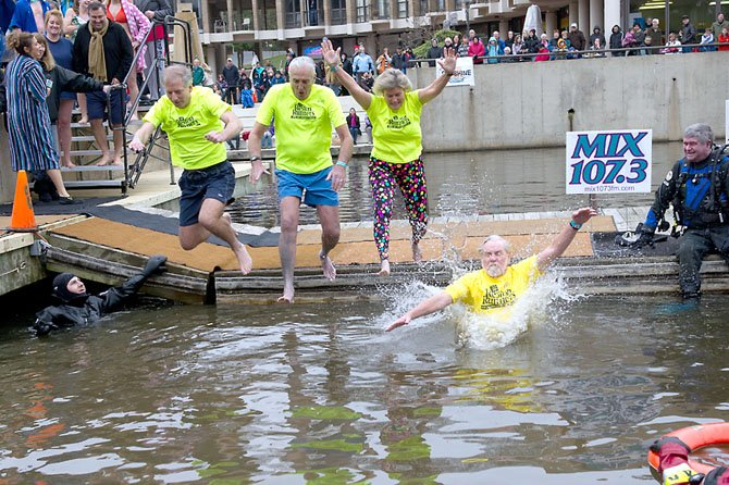 Team Reston Runners, organized by Karen Lovelace of Reston (second from right), with a collective age of 278 years, jumps into Lake Anne. Also jumping are Tim Cohn, Joe Fleig and Joe Stowers.