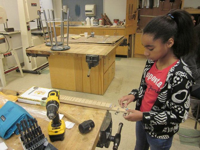 A Hammond Middle School student adjusts the tuning pegs on her cigar box guitar as part of the ASF building program.