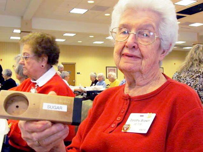 Dot Brown, one of Greenspring's volunteers, holds up a measuring cup for sugar made by residents in Greenspring's woodshop.