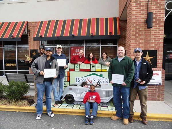 Ron Kowalski (back left) and Susan Borrelli (back right) stand with winners of last year's annual Monopoly Tournament in front of Glory Days Grill in Lorton, which hosted the event to raise money for Habitat for Humanity of Northern Virginia. This year's tournament will be held Saturday, Feb. 25 from 9 a.m. to 2 p.m. at the Workhouse Arts Center.