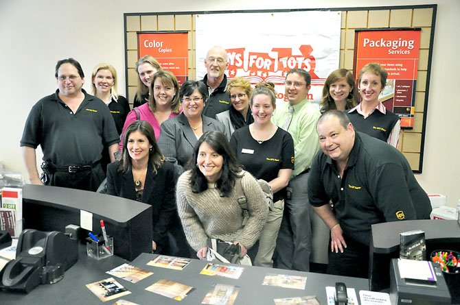 Staff from the South Lakes UPS Store, Reston elementary schools and other community groups at the UPS Store Friday, Feb. 10 after owner Hal Berens presented $10,000 worth of books to Lake Anne, Terraset and Forest Edge Elementary Schools, as well as Reston Interfaith.