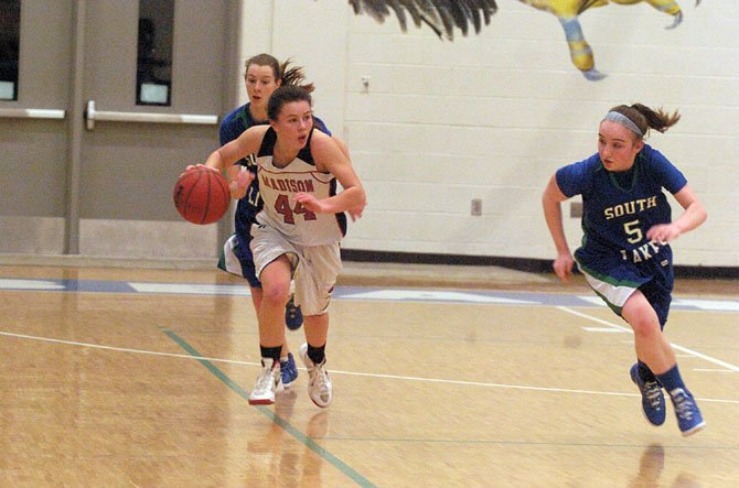 Megan LeDuc of Madison High races up the court with the ball as South Lakes' Caitlin Jensen defends. LeDuc, a junior guard, was named to the All-Tournament Team following the Warhawks' finals victory.