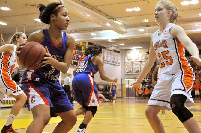 T.C. Williams junior Christian Roberts, left, is defended by West Springfield sophomore Amy Berglund during the Patriot District championship game on Feb. 17.