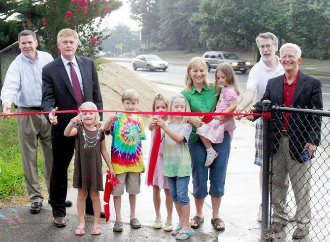 The rain didnt stop the ribbon-cutting on the new portion of sidewalk in front of Terre Centre Elementary last year. (From left) Patrick Gloyd, executive director of Burke Centre; Supervisor John Cook (R-Braddock);  Rebecca, Matthew, Claire, Lauren and mom Rachel Eliff holding Charlotte; Kevin Morse, Braddock  appointee to the FCTAC; and Tom Kennedy, Braddock appointee to the Trails and Sidewalks Committee.