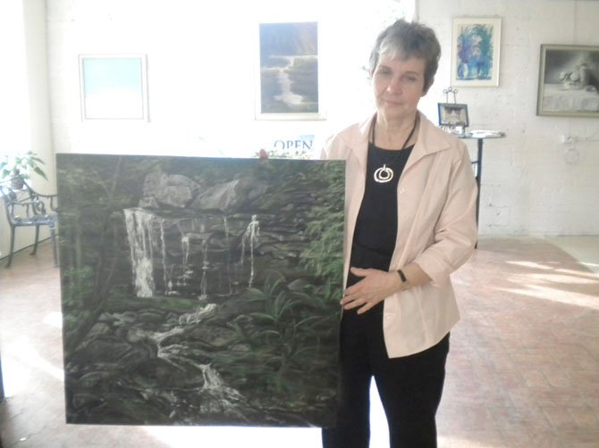 Artist Mary Hawkins with her painting of a waterfall that will be featured in this month's show, Visions of the Earth.