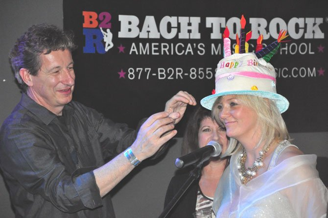 Pete DiCenso of the Dead Cat Bounce Band presents Julie Lansaw Warrin with a hat commemorating the McLean Project for the Arts 50th anniversary Friday, Feb. 24. DiCenso and his band performed the music for the evening.