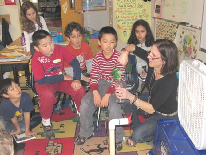 Churchill Road 2nd graders Nolan Harrison, Oliver Tu, Katherine Senich, Neil Bajaj, Aidan Nguyen and Salma Saout look on with interest as Debra Maes demonstrates how a wind turbine can be used to power an LED light.