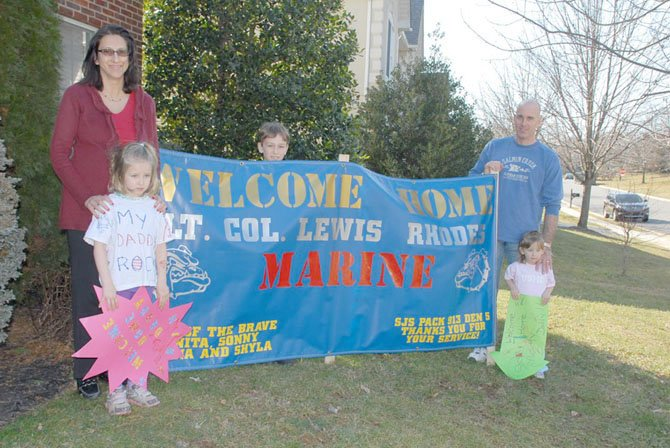 Vinita and Lewis Rhodes with their children, Sabina (on left), Sonny, and Shyla at their home in reston. Cub Scout Pack 913 ordered the blue banner that adorned the family lawn when Lewis returned home. Other neighbors and friends also made lawn signs, welcoming Lewis home.