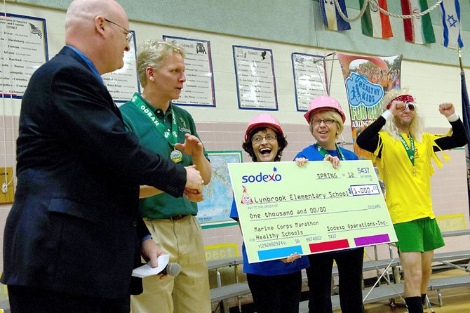 Lynbrook Elementary School Principal Mary McNamee and Assistant Principal Shirley Shannon hold a $1,000 check presented to them by Larry McMarlin of Sodexo Corporation on Feb. 8, for the school's participation in the 2011 Marine Corps Marathon Healthy Kids Fun Run on Oct. 29, 2011. From left: Larry McMarlin of Sodexo Corporation, Richard Dexter, PE teacher at Lynbrook Elementary School, Assistant Principal Shirley Shannon, Principal Mary McNamee and PE teacher Jed Bobier.
