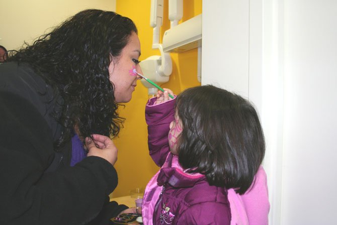 Isabelle, 2, paints a flower on her mother Ariana Laras face at Alexandria Children&#39;s Dentistry to celebrate Children&#39;s Dental Health Month.    