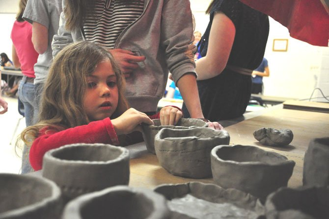 Mckenna Gurgo, 4, puts the finishing touches on her clay bowl at McLean High School Thursday, March 1.