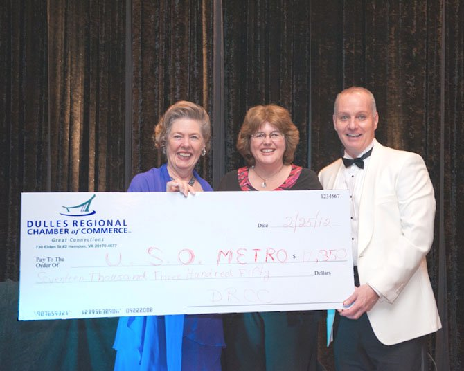 Dulles Regional Chamber President Eileen Curtis, left, and Chamber Board of Directors Chairman Kirk Forman, right, present the proceeds of the paddle auction to USO Metropolitan Washington representative Pam Horton, center.