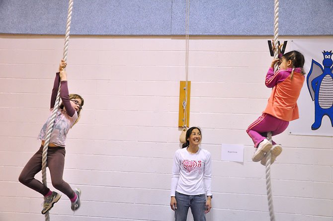 From left, Sarah McGrath and Sophia Ambrose, first graders at Colvin Rum Elementary, try to climb the gym rope while volunteer Sabrina Thomas cheers them on.