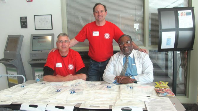 From left, Dr.Thomas Wilson, executive director of the Northern Virginia Dental Clinic in Falls Church; Dr. Peter Cocolis, chair of the 2012 Mission of Mercy Dental Fair, who has a dental practice in Springfield; and Dr. Howard Kelley of Vienna, chief dentist of NoVas Medical Education Campus, take time to greet patients and hand out literature on oral hygiene. All three were instrumental in organizing the two-day event. 