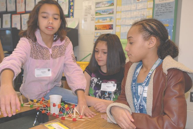 Caroline Torres, Stephanie Jimenez and Skylar Montgomery participate in the gumdrop challenge workshop Saturday at the GEMS Conference. The girls built a bridge of gumdrops and toothpicks. Pennies were dropped into the paper cup in the center of the bridge to determine how much weight the bridge could hold.