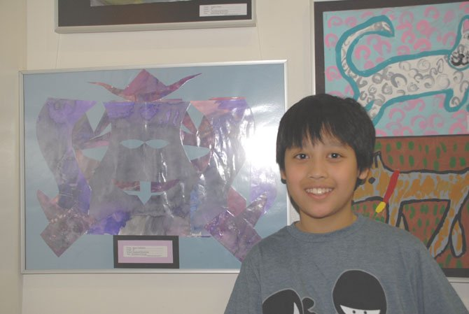Justin Yudhistira, a fifth grader at Dogwood, with his art work featuring symmetrical design.