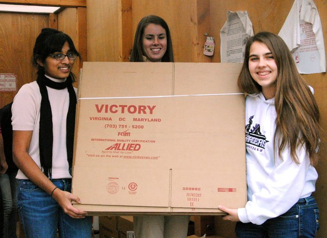 From left: Priyanka Srinivasan, Christy Quetsch and Rachel Dunning will soon help pack these flattened boxes.