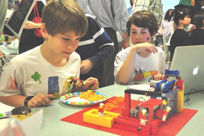 From left, Harrison Langpaul and Alec Butler, students at Colvin Run Elementary School, examine their potato chip factory made of Lego bricks during the Junior First Lego League Expo Saturday, March 17 at Colvin Run Elementary.