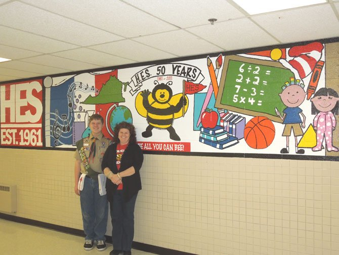 Jacob Reeves and Principal Ann Gwynn standing in front of the mural Reeves created for Herndon Elementary School's 50th year celebration.