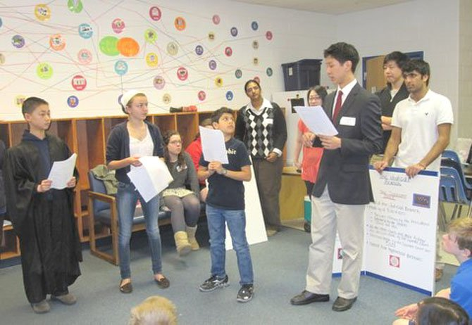 Pictured from left, re-enacting a case of a stolen iPod are Churchill Road 6th graders Chris Jiang (Judge), Valentina Deschler (Witness) and Darian Kaviani (Accused). From back left, Langley High School students Sarah Etherton, Stephanie Anderson (partially hidden), Nikita Thomas, Suzanne Kim, Jimmy Fang (Police Officer) and Nikhil Dua provide background information.