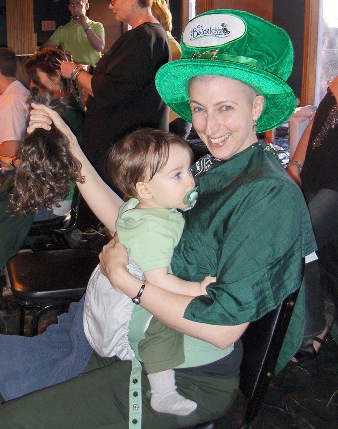 Samantha Lubkin holds her hair and her son Kai after being shaved at Centreville's St. Baldrick's day event Saturday at Fast Eddie's.