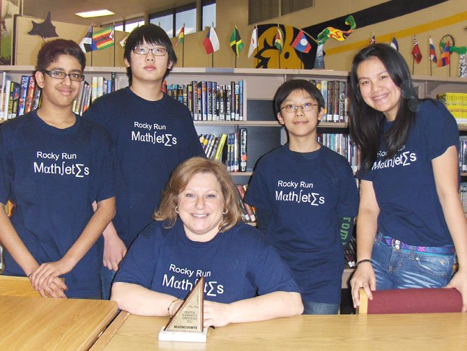 "Wearing their ""mathletes"" T-shirts are Rocky Run's MathCounts team members (from left): Rajat Khanna, team captain Robin Park, Alec Zhang and Joie Wang with coach Melanie Roller (seated) and their Chapter trophy."