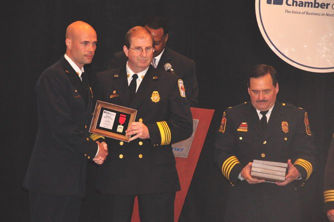 From right, Fairfax County Police Chief Col. David Rohrer and Fairfax County Fire Chief Ronald Mastin present Lt. Aron Corwin with a Bronze Medal of Valor for his efforts saving the life of five people during a swift water rescue in the Lorton area.