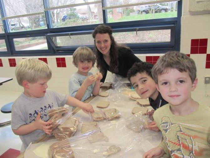 Churchill Road students begin service learning early.  Kindergartners Collin Walter, Luke Iverson, Jacob Sedaca and Jack Donohue, make sandwiches with the guidance of Jack's mom, Hannah Donahue.