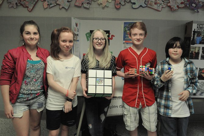 Rakey Marciniak, Christopher Tait, Anya Weber, Aubrey Trabue and Oliver McKellips show and visit the Rubik's Cube display in the hallway at Walt Whitman Middle School.