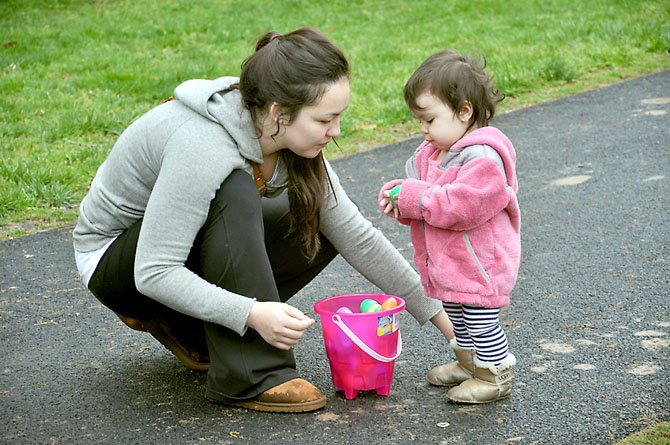 Mary Wheeler of Reston helps her 16-month-old daughter Hailey sort through her egg basket after the conclusion of the Eggnormous Egg Hunt. This year's hunt will take place Saturday, March 31.