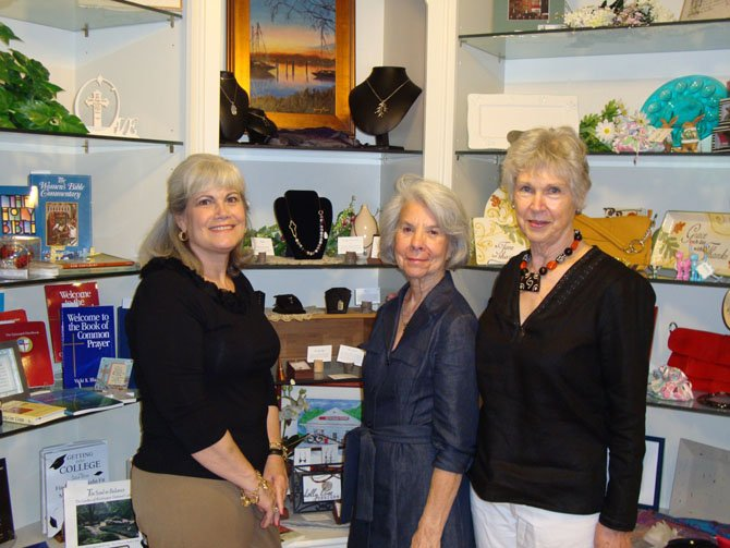 Historic Christ Church Gift Shop volunteers Holly Wright, Anna Willis and Kathy Moore (from left) present a display of jewelry by Tiffany Scott and oil paintings and reproductions by Nancy Ziegler that will be featured at an April 19 Meet the Artist exhibit at the Gift Shop.
