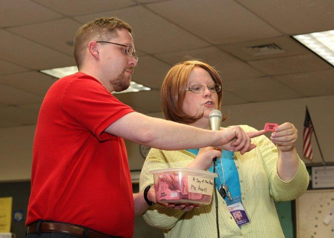 Maura Caulfield, principal, and Larry Caines, assistant principal, draw names and announce the raffle basket winners.
