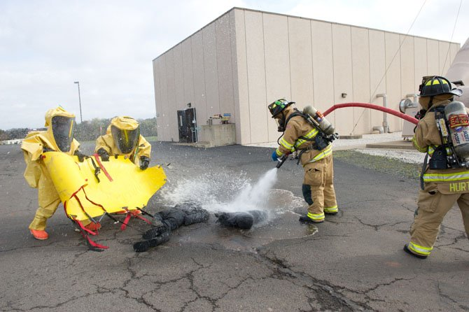 In this training scenario, the wrong chemicals have been added to a storage tank at this facility, injuring two people.  Firefighters in the Hazmat suits (on left) have just moved the two victims from the contaminated building in the rear to a decontamination area where the victims are decontaminated by other members of the Hazmat team.