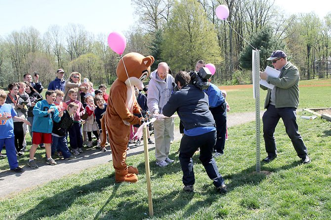 Chester the Chipmunk, the Chesterbrook Elementary School mascot, cuts the ribbon on the school's new fitness trail Monday, March 26.