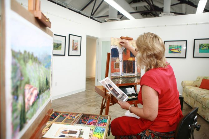 Carol Iglesias working on artwork at the Workhouse Arts Center.